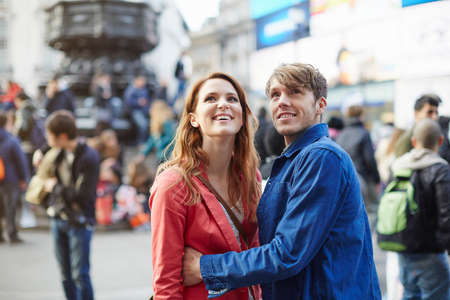 25 35: Tourist couple looking up from Piccadilly Circus, London, UK