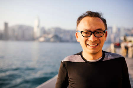 Portrait of mid adult man wearing glasses in front of water, looking at camera smiling LANG_EVOIMAGES