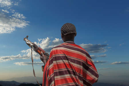 ethiopian ethnicity: Rear view of young man from Karo tribe with Kalashnikov rifle, watching his herd, Ethiopia, Africa