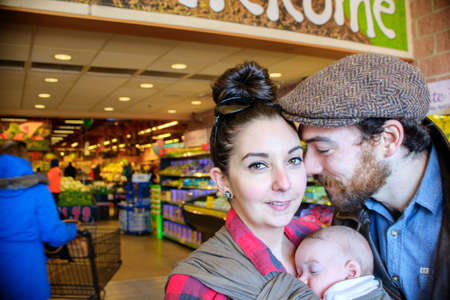 supermarket: Mother and father with baby son in supermarket