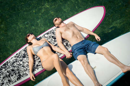 Overhead view of young couple sunbathing on paddleboards LANG_EVOIMAGES