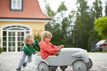 vintage: Two boys playing with vintage toy car in front of house