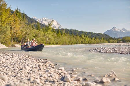 Family using paddles to steer dinghy on water, Wallgau, Bavaria, germany