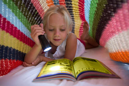 Girl lying on bed hiding under blanket and using torch to read magazine