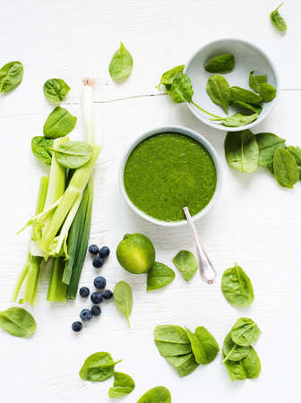 Bowl of fresh spinach soup with celery, spring onions and blueberries LANG_EVOIMAGES