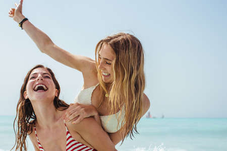 Two young female friends playing piggybacks at coast LANG_EVOIMAGES