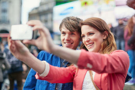 Tourist couple taking smartphone selfie at Piccadilly Circus, London, UK