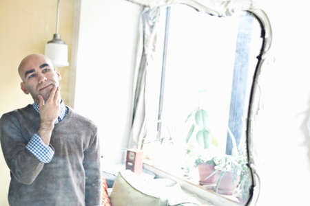 mirror image: Wall mirror reflection of young man posing with hand on chin
