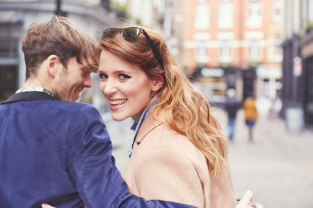 25 35: Portrait of couple strolling along street, London, UK