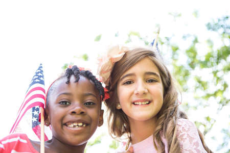 Portrait of girl with American flag in park LANG_EVOIMAGES