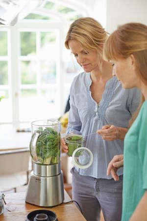 Women preparing green vegan smoothie in kitchen LANG_EVOIMAGES
