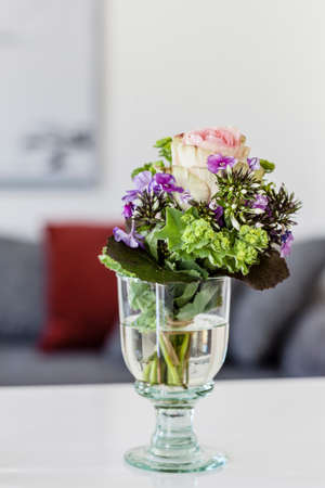 Wine glass with cut flowers on apartment coffee table