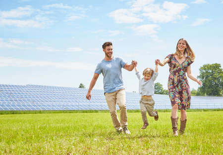 Mother and father holding hands with son, walking across field next to solar farm LANG_EVOIMAGES