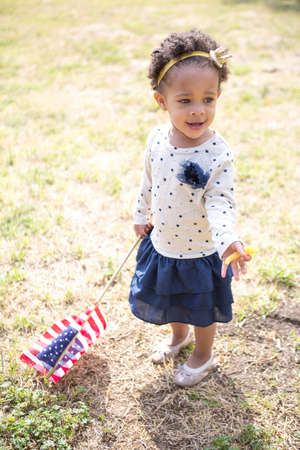 Toddler with American flag in park