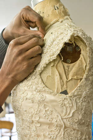 sleek: Hands of seamstress adjusting wedding dress on tailors dummy