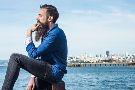 Man with beard sitting at Port Point, San Francisco, California, USA