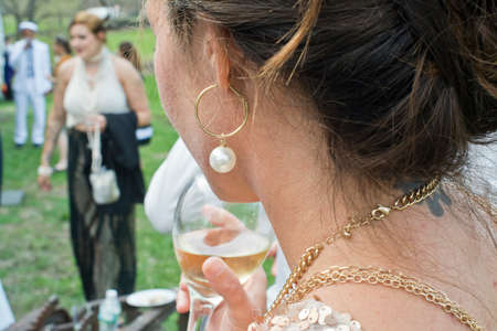 Wedding guest holding glass of wine, rear view, close-up