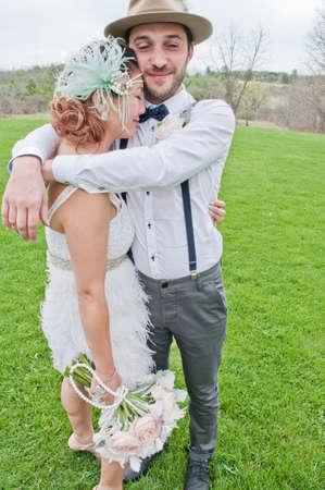 Bride and groom hugging in field LANG_EVOIMAGES