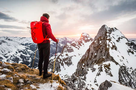 secluded: Rear view of hiker looking at snow capped mountain range, Kellenspitze, Tannheim mountains, Tyrol, Austria