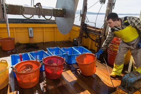 shadowed: Fisherman with baskets of shellfish