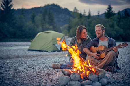 Young couple sitting by campfire playing guitar