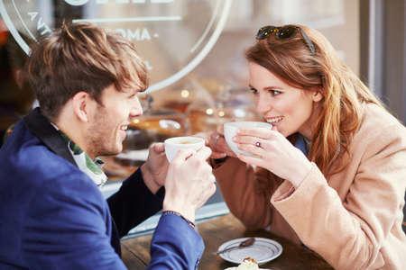 Couple drinking coffee at sidewalk cafe, London, UK