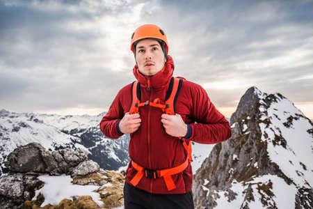 Hiker wearing helmet on mountain, Kellenspitze, Tannheim mountains, Tyrol, Austria