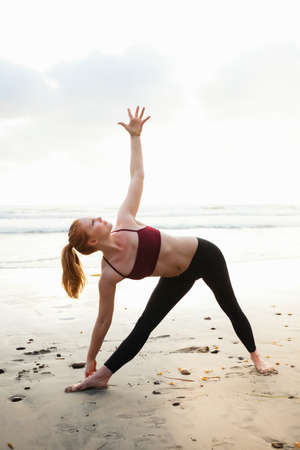 Mid adult woman practicing triangle yoga pose on beach