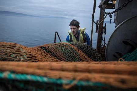 Fisherman preparing net, Isle of Skye, Scotland LANG_EVOIMAGES