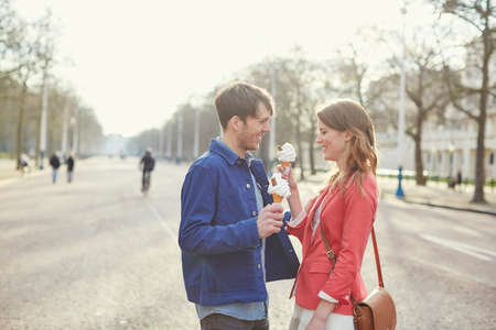 25 35: Couple eating ice cream cones in park, London, UK LANG_EVOIMAGES