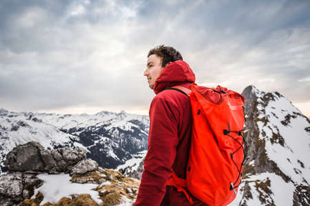 Hiker looking at snow capped mountain range, Kellenspitze, Tannheim mountains, Tyrol, Austria