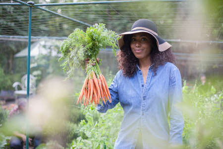 Woman holding up carrots from allotment LANG_EVOIMAGES