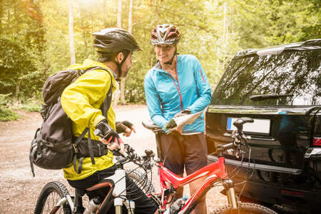Mature mountain biking couple checking map in forest car park LANG_EVOIMAGES