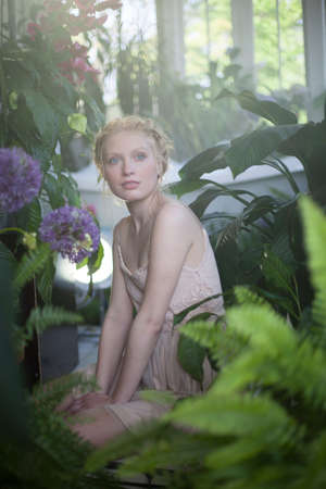 Portrait of young woman sitting in room full of plants