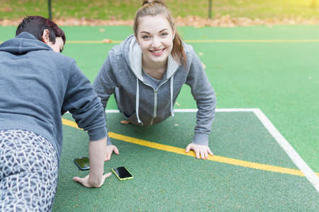 Young women with mobile phones doing push-ups on sports court, looking at camera smiling