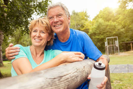 Portrait of couple, leaning on fence, holding water bottle LANG_EVOIMAGES