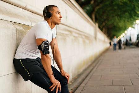 Male runner wearing headphones taking a break on riverside
