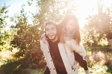 Young man giving young woman piggyback ride, outdoors