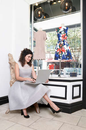 salespeople: Portrait of mature woman sitting in fashion boutique, using laptop LANG_EVOIMAGES