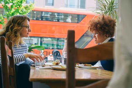 sit down: Dos amigas comiendo el almuerzo y conversando en el café LANG_EVOIMAGES