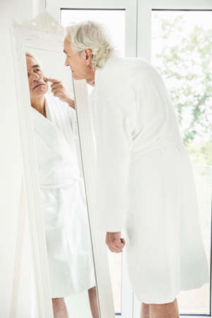 narcissist: Grey haired senior man wearing bathrobe staring at himself in mirror