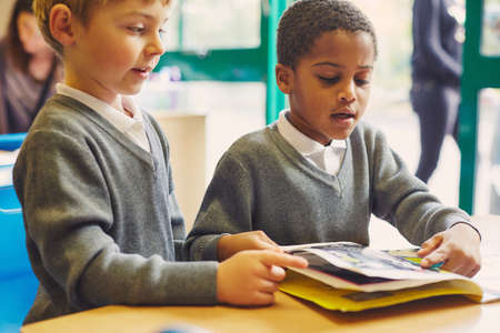 Two boys doing reading storybook at desk in elementary school classroom