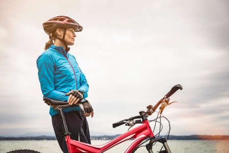 Mature female mountain biker looking out from lakeside LANG_EVOIMAGES
