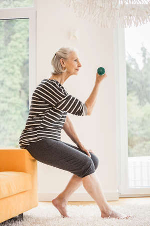 Senior woman sitting on sofa exercising with dumbbell LANG_EVOIMAGES