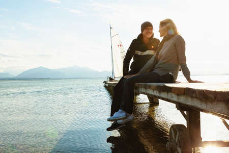 Mature couple sitting on jetty, smiling