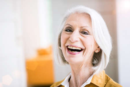 Portrait of senior woman looking at camera open mouthed smiling LANG_EVOIMAGES