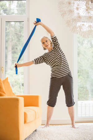 Senior woman exercising in living room using resistance band