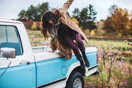 transportation: Young woman jumping from back of truck LANG_EVOIMAGES