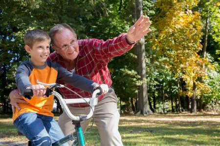 Senior man directing grandson on bicycle in woods