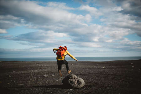 liberating: Rear view of mid adult man jumping over boulder on volcanic landscape, Iceland